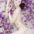 Attractive naked girl enjoys a bath with milk and rose petals. Spa treatmen - 图库照片