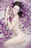 Attractive naked girl enjoys a bath with milk and rose petals. Spa treatmen — Stock Photo