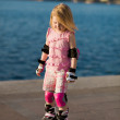 Young pretty girl on rollerskates in the park — Stock Photo