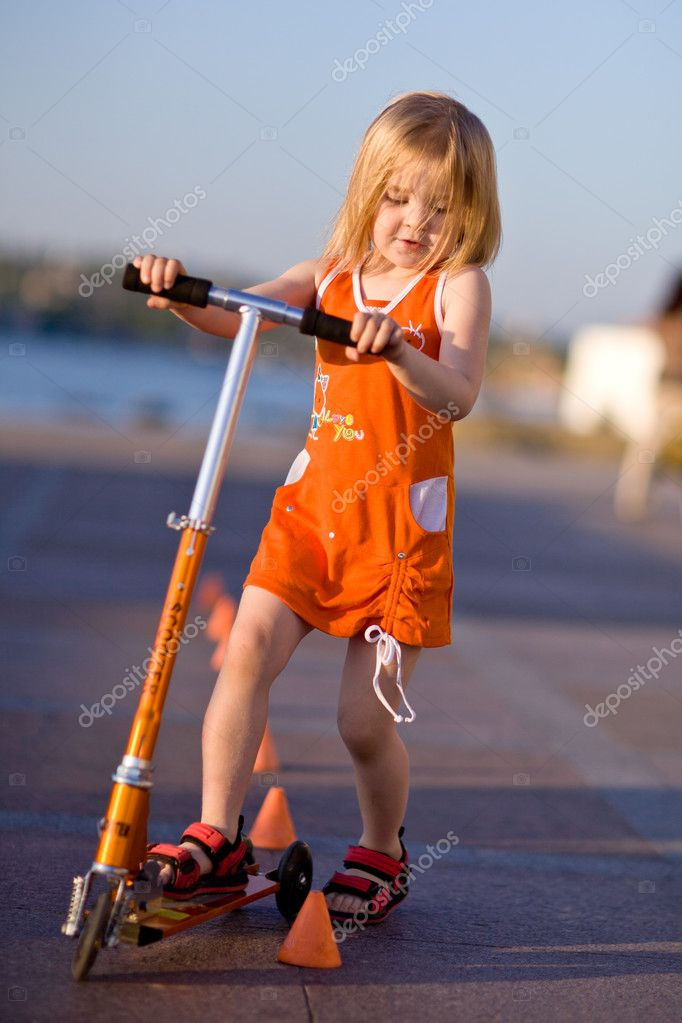 Pretty girl riding a scooter  Stock Photo #5750925