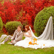 Joyful bride and groom on grass in park — Stock Photo