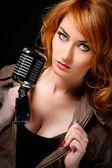 Beautiful redhead woman with retro microphone — Stock Photo