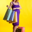 Pregnant woman looking inside shopping bags — Stock Photo