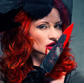 Gorgeous redhead woman with bloody knife in her hand close-up — Stock Photo