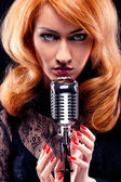 Beautiful redhead girl with retro microphone — Stock Photo