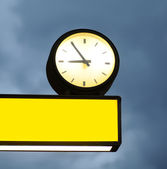 Empty signboard and clock over blue sky background — Stock Photo