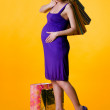 Lovely pregnant woman holding shopping bags — Stock Photo #5889355