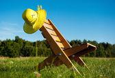 Poltrona e cappello di paglia outdoors — Foto Stock