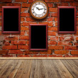 Foto de Stock  : Empty photo frames and watch against brick wall in old room