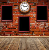 Empty photo frames and watch against an brick wall in old room — Stock Photo