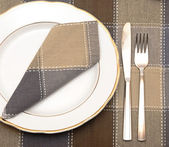 Knife and fork with white plate on wooden table — Stock Photo