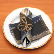 Knife and fork in textile napkin on wooden table — Stock Photo