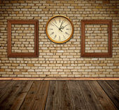 Empty photo frames and wall clock against an wall in old room — Stock Photo