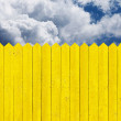 Yellow picket fence and sky clouds — Stock Photo