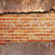 Torn metal texture over brick wall background — Stock Photo