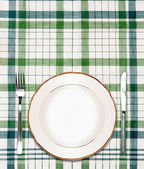 White plate on green checkered tablecloth with knife and fork — Stock Photo
