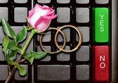 Wedding rings and red roses on computer keyboard — Stock Photo