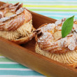 Choux Pastry in wooden plate - Stock Photo