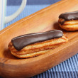 Eclairs on blue table cloth - Stock Photo