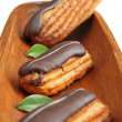 Eclairs on wooden plate - Stock Photo