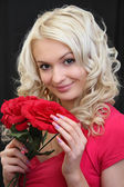 Beautiful blonde with red flowers. — Stock Photo
