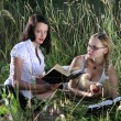 Two girls on  grass, with books. — Stock Photo