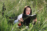 Girl on grass, with books. — Stock Photo