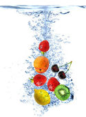 Fruit splashing into the water — Stock Photo