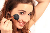 Young happy woman with make-up brush — Stock Photo