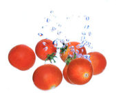 Fresh cherry tomatoes dropped into the water — Stock Photo