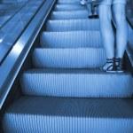 Escalator with female legs — Stock Photo