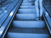 Escada rolante com pernas femininas — Foto Stock
