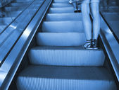Escalator with female legs — Stok fotoğraf