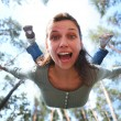 Woman falls from above the pine forest directly at you. - Stock Photo