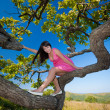 Active girl sitting on a branch — Stock Photo