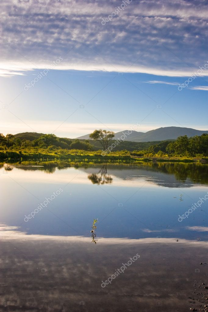 Azure lake with a reflection of the clouds of heaven at the foot of the mountains — Stock Photo #5606702