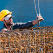 Construction worker loading stack of reinforcement beam cages to - Stock Photo