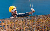 Construction worker loading stack of reinforcement beam cages to — Stock Photo