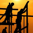 Construction workers under a hot blazing sun - Stock Photo