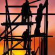 Stock Photo: Construction workers against colorful sunset