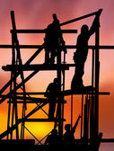 Construction workers against colorful sunset — Stock Photo