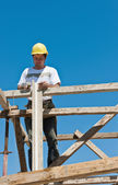 Construction worker on scaffold busy with formwork preparation — Stock Photo