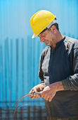 Construction worker cutting wire with pair of pliers — Stock Photo