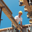 Construction worker placing formwork beams - Stock Photo