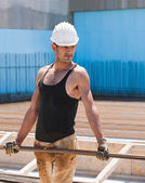 Construction worker carrying reinforcement steel bars — Stock Photo