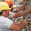 Stok fotoğraf: Construction workers positioning cement formwork frames