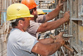 Construction workers positioning cement formwork frames — Stockfoto