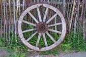 Sola rueda de carreta antigua cerca de la valla de madera — Foto de Stock