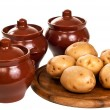 Clay pots and fresh appetizing potato on a cutting board. — Stock Photo
