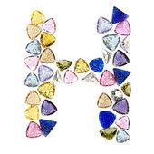 Gemstones alphabet, letter H. Isolated on white background. — Stock Photo